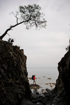 Woman standing between the rocks on the coastline on the sea with hiking backpack