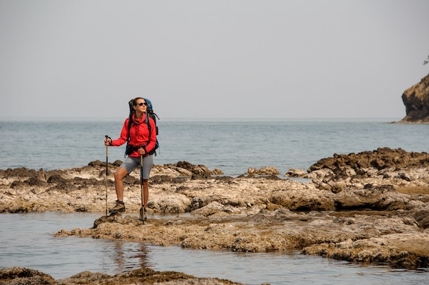 Woman standing on the rocks on the sea with hiking backpack