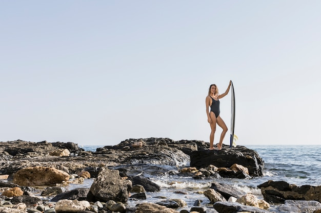 Woman standing on rocky sea shore with big surfboard