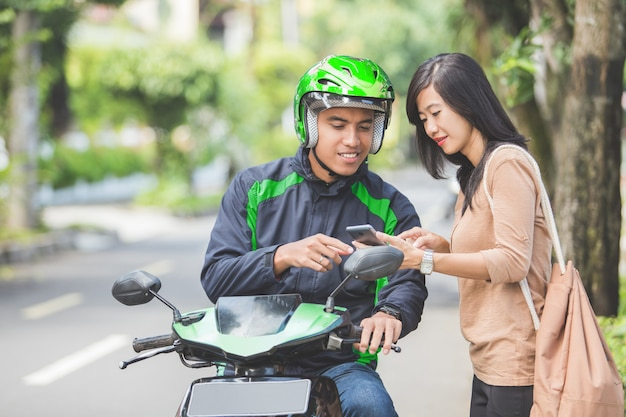 Woman standing on sidewalk ordering a commercial motorcycle taxi