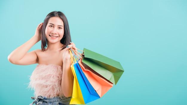 多色の買い物袋を保持している彼女のショッピング夏の女性立っている笑顔