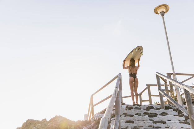 Woman standing on stairs with surfboard on head