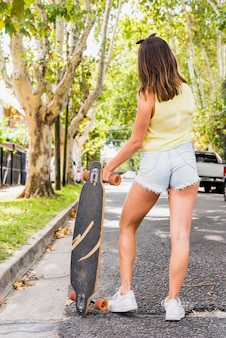 Woman standing on street and holding longboard