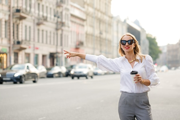 Woman standing on the street with coffee and catches a car