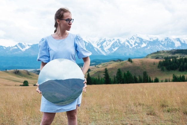 Woman standing in in summer altai mountains in kurai steppe and holding circle mirror creative trave...