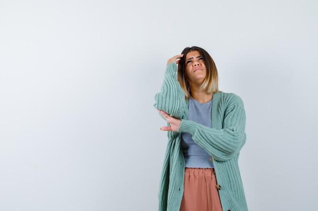 Donna in piedi nel pensiero posa in abiti casual e guardando cupo, vista frontale.