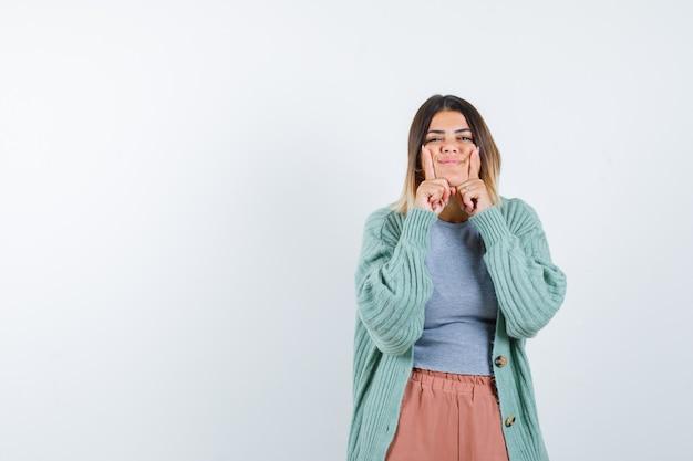 Donna in piedi nella posa di pensiero in abiti casual e che sembra allegra. vista frontale.