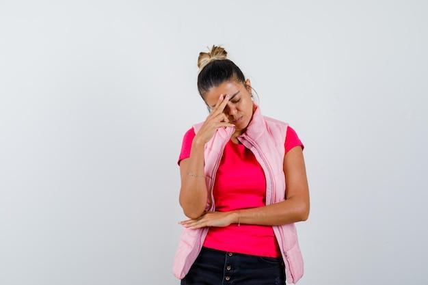 Donna in piedi in posa di pensiero in maglietta, gilet e sembra triste