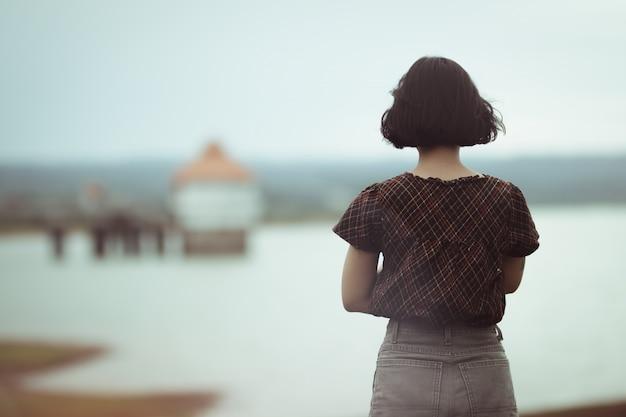 Женщина, стоящая думать о чем-то с одиноким.