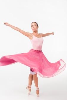 Woman standing on tiptoe wearing pink tutu swinging against white backdrop