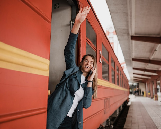 Woman standing in the train entrance and waving