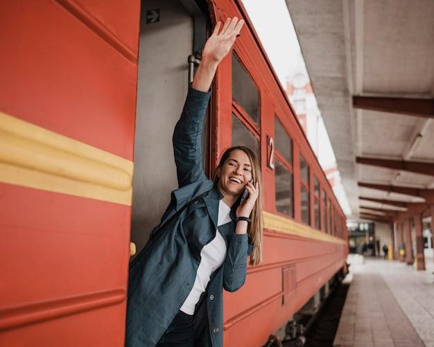 Donna in piedi all'ingresso del treno e agitando