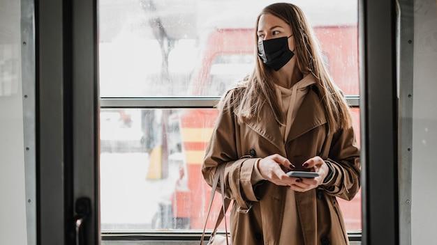 Donna in piedi in un treno e guardando lontano