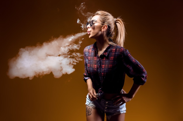 Woman standing and vaping in studio