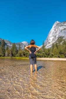 Donna in piedi nell'acqua di fronte alle montagne del parco nazionale di yosemite