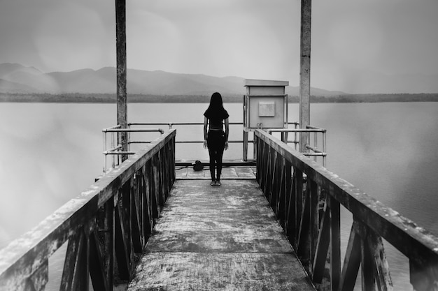 Woman standing at water level gate, horror scene in white tone