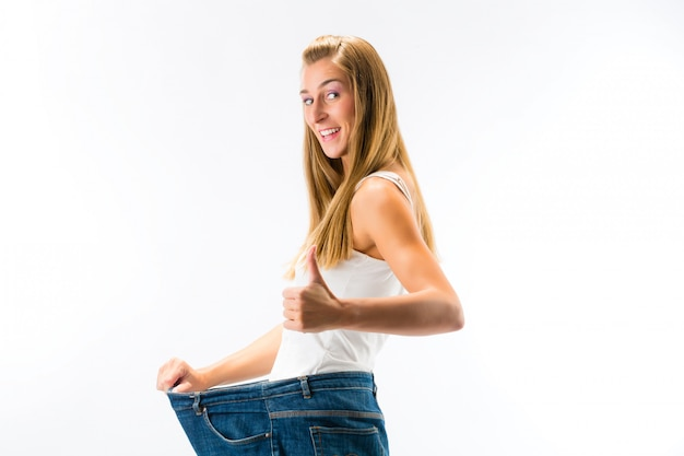 Woman standing and wearing a too big pants after loosing weight