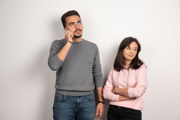 전화로 얘기하는 남자 동안 서있는 여자.