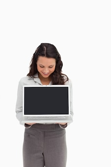 Woman standing while showing a laptop screen