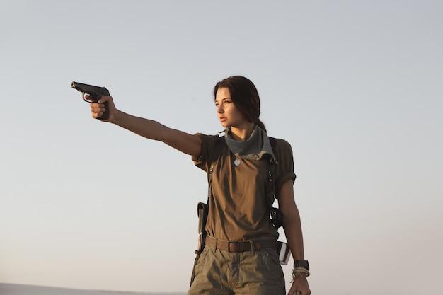 砂漠の屋外で銃を持って立っている女性