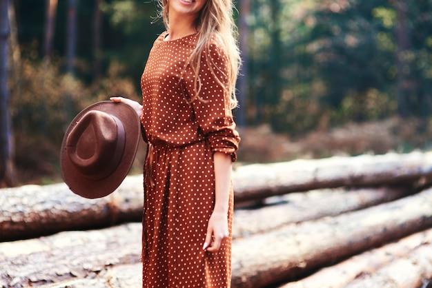 Женщина, стоящая в осенней шляпе