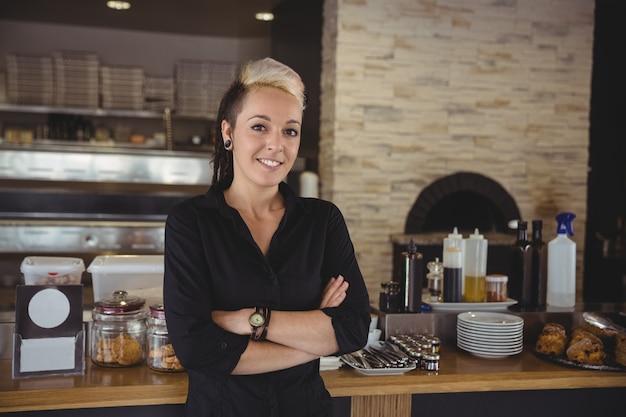 腕を組んでキッチンで立っている女性