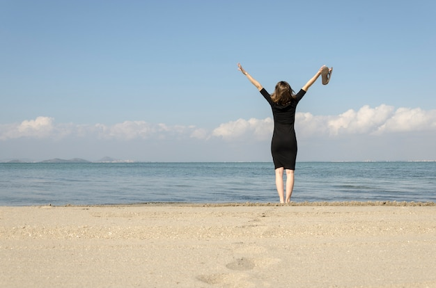 Woman standing with arms outstretched on the beach at sea