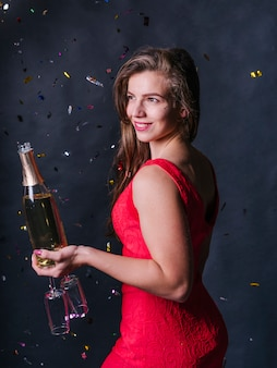 Woman standing with champagne bottle and glasses