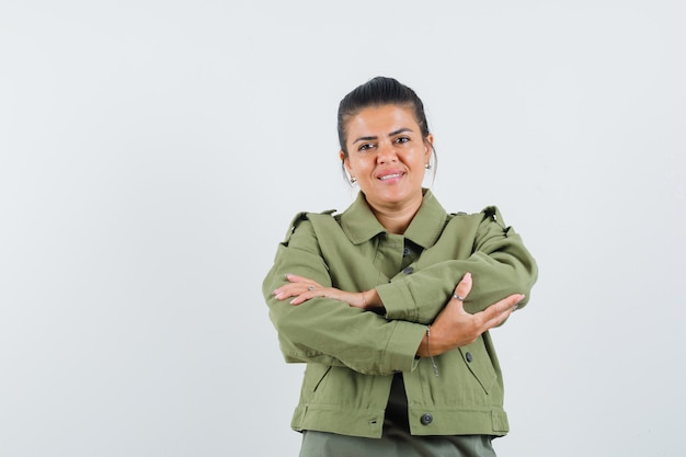 Woman standing with crossed arms in jacket, t-shirt and looking cheery