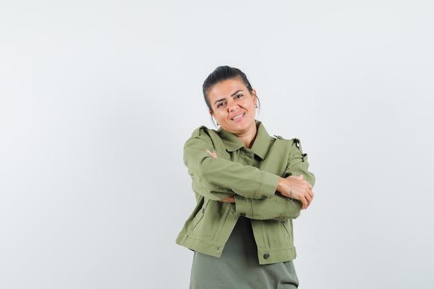 Donna in piedi con le braccia incrociate in giacca, t-shirt e guardando fiducioso