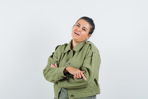 Woman standing with crossed arms in jacket, t-shirt and looking confident