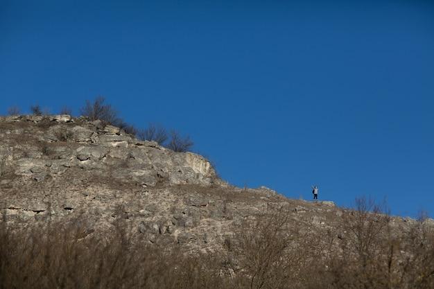 바위 산에 손을 들고 서 있는 여자
