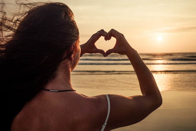 海に背を向けて立って、夕日に対して彼女の指からハートを作る女性
