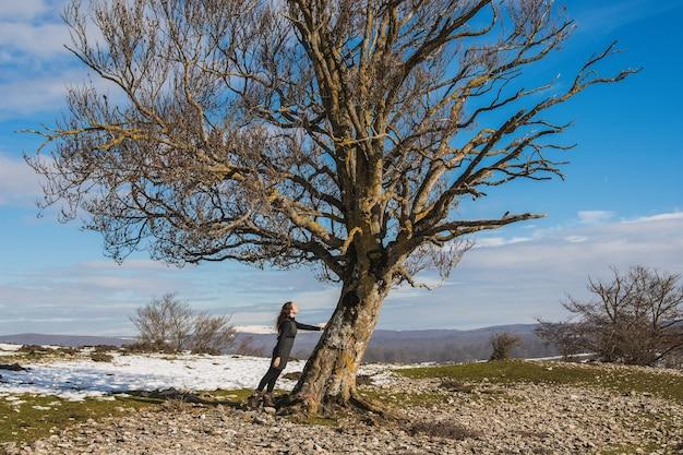 雪と土のある冬の風景の真ん中に大きな葉のない木に手を置いて立っている女性。環境への配慮