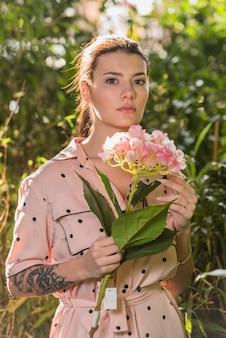 핑크 꽃 손에 서있는 여자