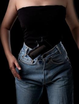 黒の背景にピストル銃で立っている女性拳銃を運ぶ若いセクシーな女の子