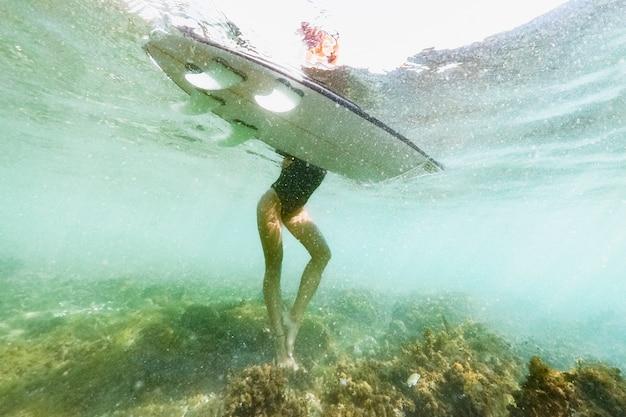 바다에서 서핑 보드와 함께 서있는 여자