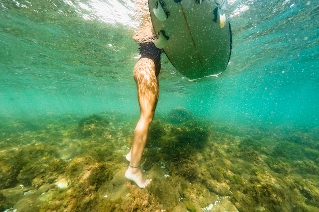 Женщина стоит с доской для серфинга в море