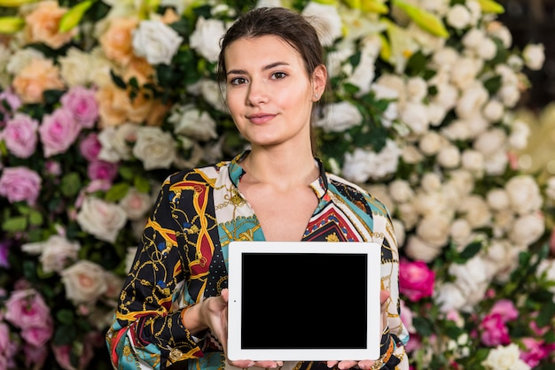 Woman standing with tablet in green house