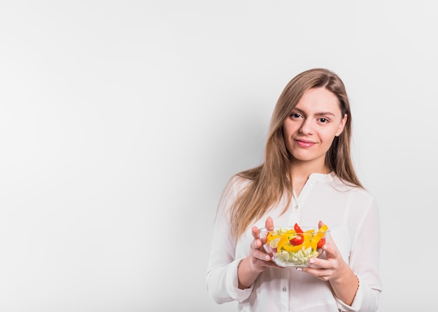 Woman standing with vegetable salad in bowl
