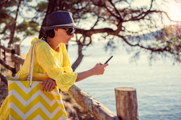 Woman standing at a wooden fence and using smart phone