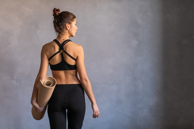 Woman standing at work out or yoga class with rolled fitness mat in her hads turned her back to the camera. copy space on dark background