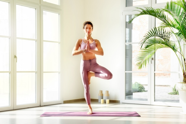 Woman standing in yoga tree pose indoors