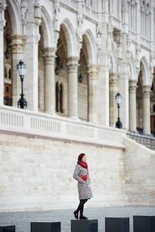 Woman stands against the backdrop of a powerful european architectural structure