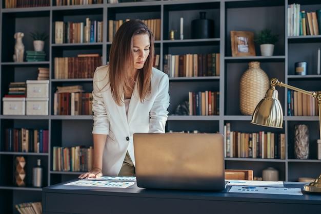 여자는 책상에 서서 문서를 살펴 봅니다.
