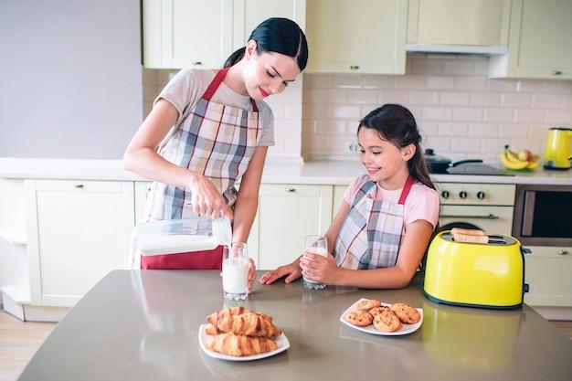 여자는 유리 컵에 테이블과 붓는 우유에 서있다. 소녀는 어머니 외에 서서 그것을 본다. 그녀는 손으로 컵을 들고 있습니다. 테이블에 롤과 노란색 토스터가 있습니다.