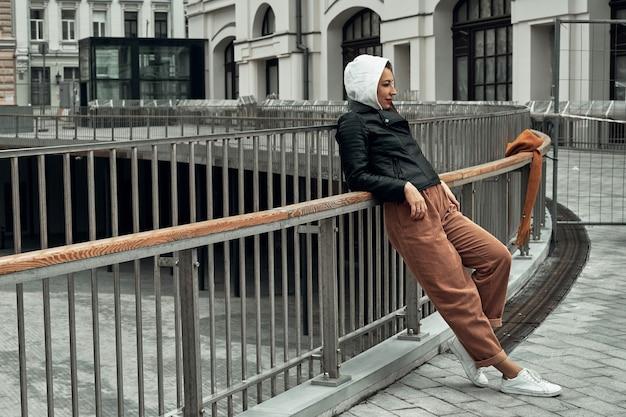 Женщина стоит у забора на мосту в городе.
