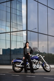 Woman stands in front of a motorcycle in front of a glass building in a parking lot near a shopping center.