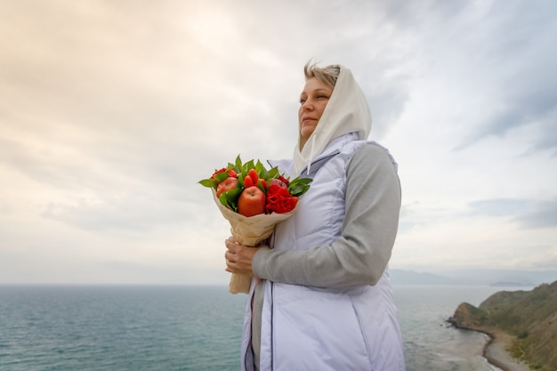 Woman stands on a high hill with a bouquet in her hands