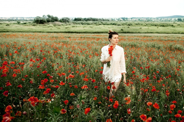 Woman stands holding a poppies flower bouquet, among the meadow of poppies